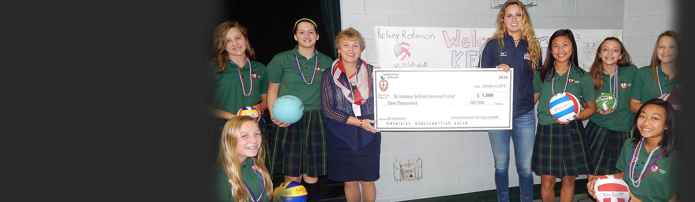 2006 St Isidore grad Kelsey Robinson,a member of Team USA's National Women's Volleyball and plays professionally overseas, presents a check to the St. Isidore Annual Alumni Fund to Mrs. Collins and members of the SIS 8th grade girls' volleyball team. See story on Kelsey's visit under Featured News.
